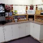 Clean breakfast counter with 2 cereals, and packaged sweet rolls, coffee, and juice machines.  T