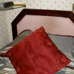 Single bed with loose headboard, narrow room
