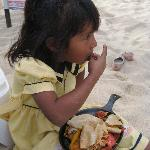 Adorable child eating yummy food on gorgeous beach.