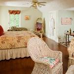 Rose Suite - A feminine room with white wicker and flowers plus a Jacuzzi tub combined with the