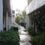 Walkway by building towards fenced pool area