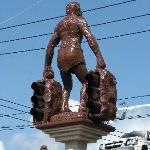 Neanderthal statues holding up traffic lights