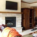 The living room with a fire place and flat screen tv.