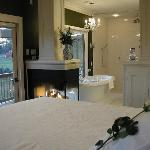 The king sized bed with view of the fireside hot air bubble massage tub for two and view of the