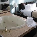 Heart-shaped jacuzzi next to king bed