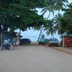 "The main street ends at the beach. At the left you can see a ""guagua"" (van) and ""motoconchos"" (m"
