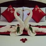Origami sawn towels and flower petals on bed