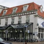Hotel building has a pub attached (glass covered area)