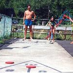 Shuffle board, horseshoes, near the playground near the pool.