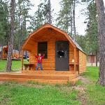 Front of cabin--campground loop road is behind it as well as vault toilet