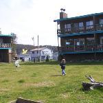 girls flying kites on lawn of High Tide