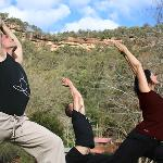 Yoga on the lawn with view up to sandstone cliffs.