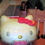 the hello kitty car parked beside the kitty's house