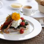 Brushetta with cherry tomato confit, baby spinach, poached eggs and crispy Parmaham