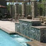 Our outdoor pool waterfall has benching seating beneath it so you can enjoy the cascading water.