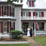 The newely weds on the front porch of the house