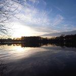 winterlicher Sonnenuntergang mit gefrorenem See