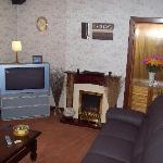 cosy sitting room with new wide screen tv  and recliner leather couches
