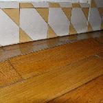 """Moderna"" -- the buckling wood floor in front of the shower stall."