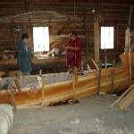 Craftsmen constructing a birch bark canoe.