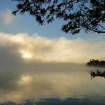 The sun coming up in the morning dispersing the mist over the lake