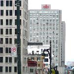 Hotel tower with a view down Ste. Catherine Street--building with logo on top.