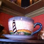 """Cape Hatteras Lighthouse """"big"""" cup and saucer on a shelf"""