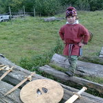 A young villager explaining the use of the axe, sheild and swords.