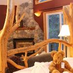 Hand Peeled Log Beds and River rock fireplaces add to your romantic getaway