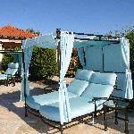 comfortable double chaises by the swimming pool