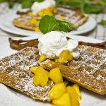 12-grain Belgian Waffles with fresh peach compote and whipped cream served with Alder-smoked bac