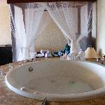 Jacuzzi bath and bed in room