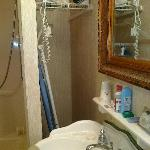 sink too close to shower to possibly lift the ironing board; wall mount hair dryer on 'shelf'