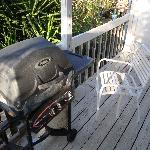 Rusty uselss grill on warn deck with broken chair.