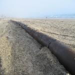 Rusted pipe adorning beach