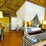 An authentic Balinese Bungalow with a thatched rooftop and a shady terrace facing the rice field