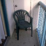 one of the two dirty old chairs on the balcony