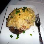 Twice baked potatoe, shown with fork to see the enormous size