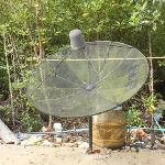 Unsightly satellite dish next to the hotel, surrounded by trash.