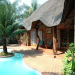 Most rooms under thatach near pool in tropical garden
