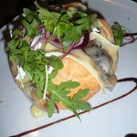 Bread load stuffed with mushrooms and melted brie, topped with arugula and drizzled with balsami