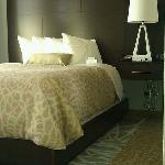 Queen bed with modern headboard and carpet tiles