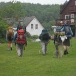 Hikers returning from trail head up the lawn from Kent Pond to the lodge