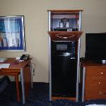 desk, mini-fridge, microwave, and tv