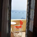 Door from sleeping area to balcony, with view of sea and caldera.