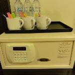 The safe and the free bottled water, sugar, coffee, tea bag, stirrer, and the cup