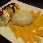 Coconut sticky rice, mango slices, mango ice cream, and whipped cream and a cherry