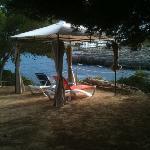 detalle terraza, tumbonas bajo pérgola, jardín frente al mar