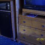 tv, microwave, and refrigerator across from beds