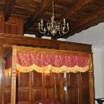 The bed with the wood-beamed ceilings and wood walls.